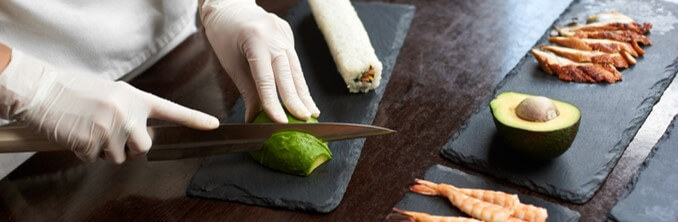 Sushi chef cutting avocado