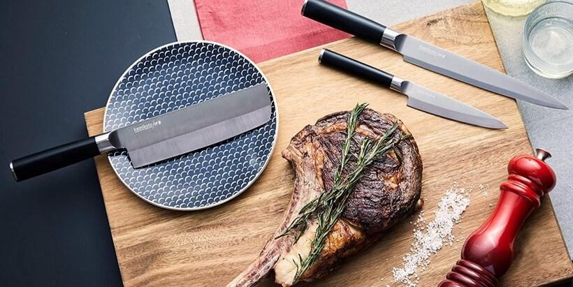Kamikoto slicing knife, utility knife, and nakiri with steak on cutting board