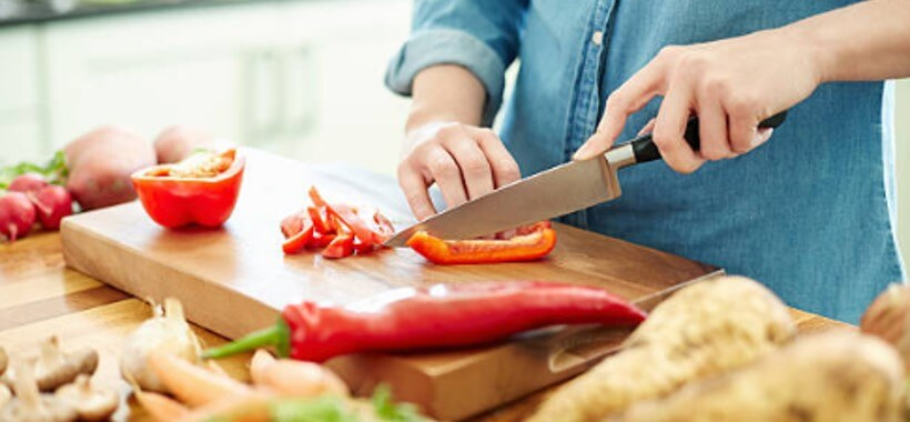 woman using steel knife to cut vegetables